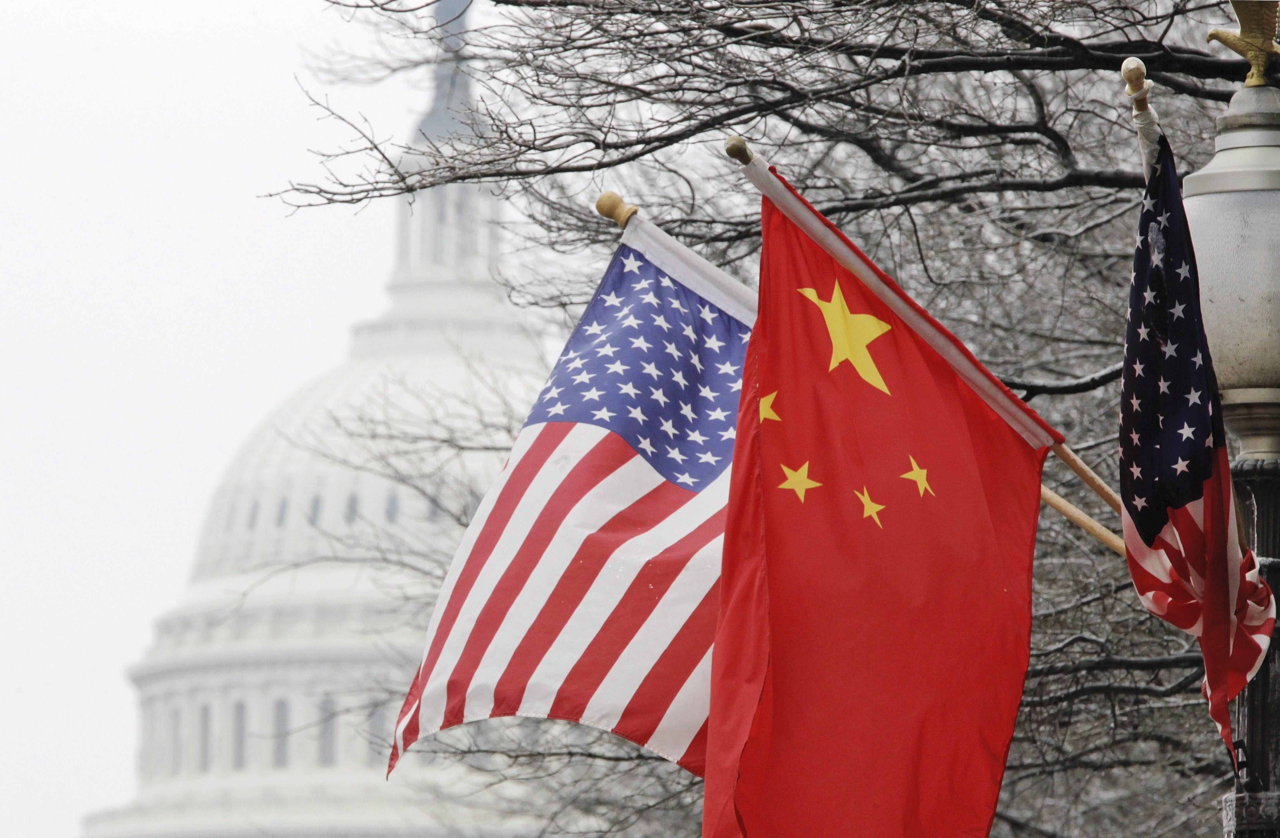 The Capitol dome is seen at rear as Chinese and U.S. flags are displayed in Washington, Tuesday, Jan. 18, 2011, ahead of the arrival of China's President Hu Jintao for a state visit hosted by President Barack Obama. (AP Photo/Charles Dharapak)